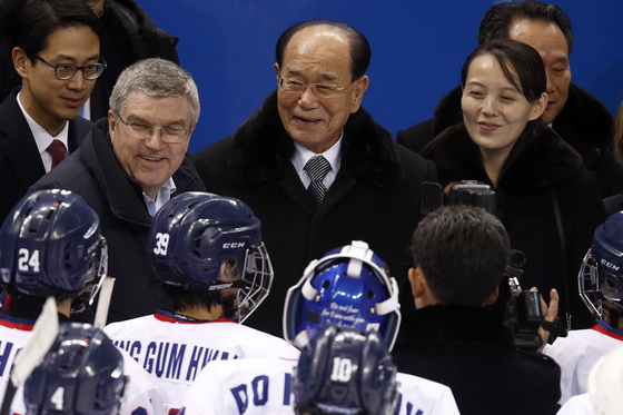 International Olympic Committee President Thomas Bach, left, then North Korean nominal head of state Kim Yong-nam, center, and Kim Yo-jong, right, the North Korean leader's sister, greet players after a women's hockey game between Switzerland and an inter-Korean team at the PyeongChang Winter Olympics in Gangneung in February 2018. North Korea decided recently not to participate in the upcoming Tokyo Olympics because of coronavirus concerns. [AP/YONHAP]