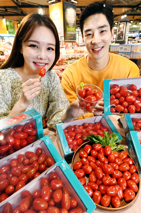Models pose with cherry tomatoes that come with the stalk removed at Homeplus' Gangseo branch in western Seoul on Wednesday. They are easy to eat and decrease food waste, according to the retailer. [NEWS1]