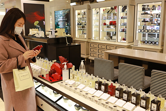 A customer looks at perfume products at a Lotte Department Store in Seoul. Lotte Department Store resumed its in-store beauty product testing service in early March when social distancing measures were eased. [LOTTE SHOPPING]