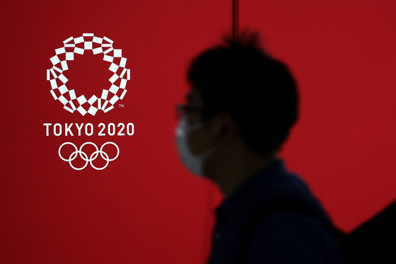 A pedestrian walks past a Tokyo 2020 Olympics logo in Japan Wednesday. Japanese Prime Minister Yoshihide Suga on Tuesday called North Korea's decision to skip the Tokyo Olympics a unilateral announcement. [AFP/YONHAP]