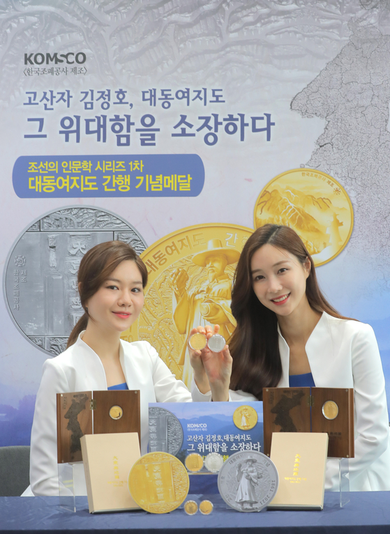 Models pose with commemorative coins marking the 160 year anniversary of the publication of Daedongyeojido at the Korea Minting, Security Printing & ID Card Operating building in Mapo District, western Seoul. Daedongyeojido is a 19th-century map of the Korean Peninsula made by Kim Jeong-ho. [YONHAP]