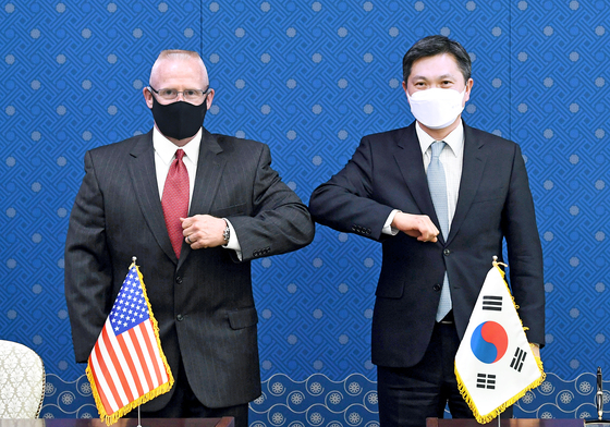 Kim Sang-jin, director general of the Korean Defense Ministry's international policy bureau, right, and Maj. Gen. Thomas Weidley of the U.S. Forces Korea bump elbows after the formal signing of the defense cost-sharing deal in Seoul Thursday. [YONHAP]