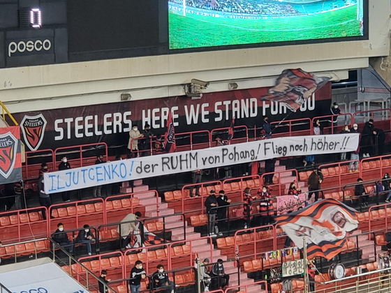 """Pohang Steelers fans hold up a banner written in German that translates to """"Iljutcenko, the pride of Pohang, fly even higher!"""" [YONHAP]"""