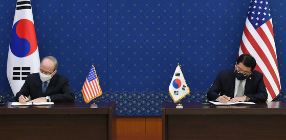 Korean First Vice Foreign Minister Choi Jong-kun, right, and Rob Rapson, charge d'affaires at the U.S. Embassy, formally sign the 11th Special Measures Agreement at the Foreign Ministry in central Seoul Thursday afternoon. [JOINT PRESS CORPS]
