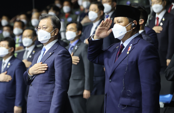 President Moon Jae-in, left, and Indonesian Defense Minister Prabowo Subianto salute the South Korean at Friday's official rollout of the KF-21 Boramae. [YONHAP]