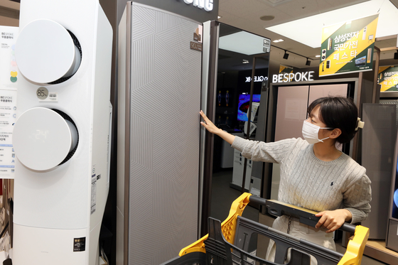 A shopper checks out an air conditioning unit at an E-mart in Seoul. Due to rising temperatures, airconditioner sales have risen sharply according to E-mart. Sales between March 1 and April 8 increased 52.2 percent year-on-year. [YONHAP]