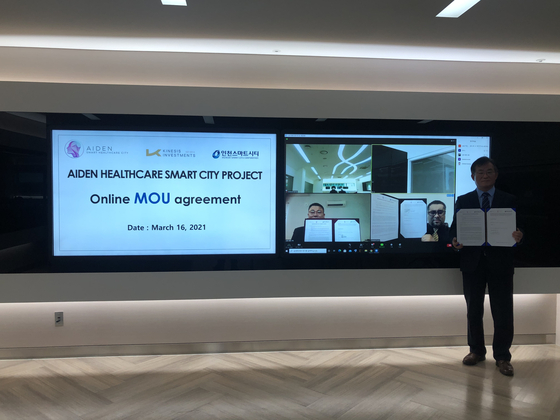 Incheon Smart City CEO Seong Ki-wook, right, holds up a MOU signed on AIDEN Healthcare Smart City Project online in March. [IFEZ]