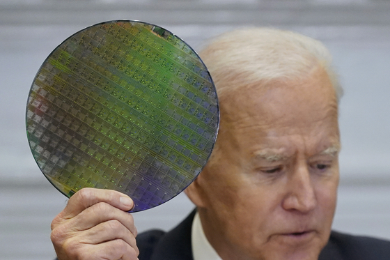 U.S. President Joe Biden holds up a silicon wafer as he participates virtually in the CEO Summit on Monday in Washington. [AP]