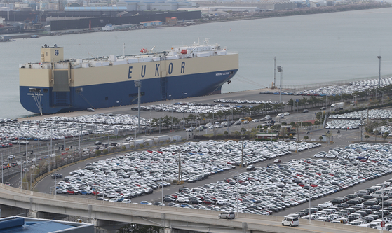 Vehicles sit ready for loading in Ulsan in March. [YONHAP]