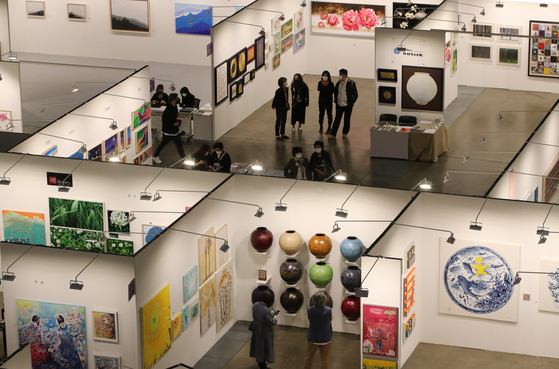 Visitors look at artwork at the 2021 Busan Annual Market of Art on April 11, which was held at Bexco, or the Busan Exhibition and Convention Center. Some 40,000 works of art from a total of 176 art galleries were exhibited at the fair. [SONG BONG-GEUN]