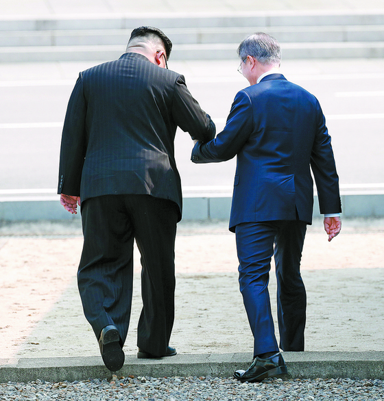 South Korean President Moon Jae-in and North Korean leader Kim Jong-un cross the Military Demarcation Line to the northern side during a summit in Panmunjom on April 27, 2018. [JOINT PRESS CORPS]