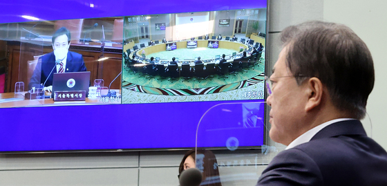 President Moon Jae-in, right, exchanges greetings with Seoul Mayor Oh Se-hoon, shown left in the screen hung on the wall, during the video conference cabinet meeting on Tuesday. Moon joined the meeting from the Blue House, while Oh and some other ministers joined from the government complex buildings in Seoul and Sejong. [YONHAP]