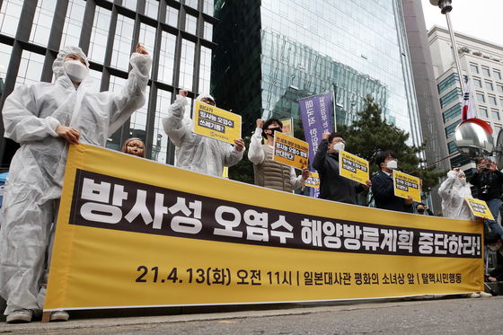 Environmental activists protest the Japanese government's decision to release contaminated water into the Pacific Ocean from its Fukushima nuclear power plant near the Japanese Embassy in central Seoul Tuesday. [NEWS1]