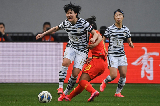 Korea's Lee Geum-min, left, and China's Tang Jiali compete for the ball during the qualifying play-off second leg women's football match at Suzhou Olympic Sports Centre Stadium in Suzhou, China on Tuesday. [AFP/YONHAP]