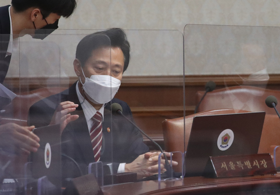 Seoul Mayor Oh Se-hoon, right, prepares to attend the cabinet meeting at the Central Government Complex in Seoul on Tuesday. [NEWS1]