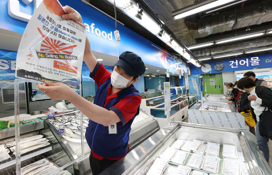 """A fishmonger at a supermarket in Dobong District, northern Seoul, hangs up a sign Tuesday that states """"Japanese seafood exports are not sold"""" after Tokyo decided to release radioactive water into the sea from its Fukushima nuclear power plant, a move also protested by Japan's fishermen. [YONHAP]"""