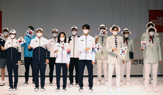 Team Korea members pose in their uniforms for the 2020 Tokyo Olympics at the National Training Center in Jincheon, North Chungcheong, on Wednesday. The new uniforms, with athletic outfits made by North Face and suits for the opening and closing ceremonies designed by Kolon Industries brand Cambridge Members, were unveiled to mark D-100 until the Games begin. [YONHAP]