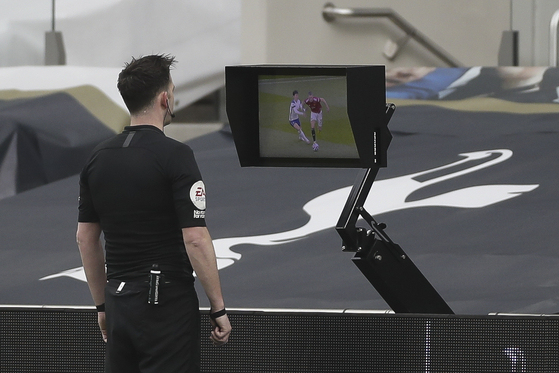 Referee Chris Kavanagh checks the video assistant referee (VAR) system for a goal decision during the English Premier League match between Tottenham Hotspur and Manchester United in London on April 11. [EPA/YONHAP]