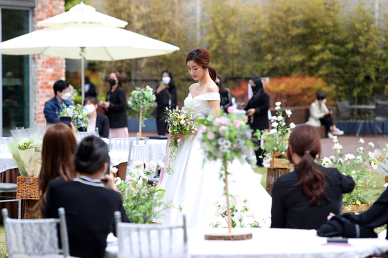 A model poses at a wedding demonstration in the outdoor roof garden of Lotte Department Store's Daegu branch, in Buk District, Daegu. According to Lotte Department Store, small weddings are becoming popular amid the Covid-19 pandemic.[YONHAP]