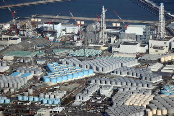 An aerial view shows tanks containing contaminated water at the Fukushima Daiichi nuclear power plant in Fukushima prefecture, northeastern Japan, on Feb.14, 2021. The Japanese government on Tuesday officially decided to release treated water in two years.  [EPA]
