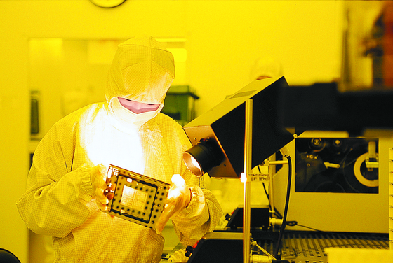 A researcher at ISC examines a component for semiconductor test socket at the company's factory in Ansan, Gyeonggi. [ISC]
