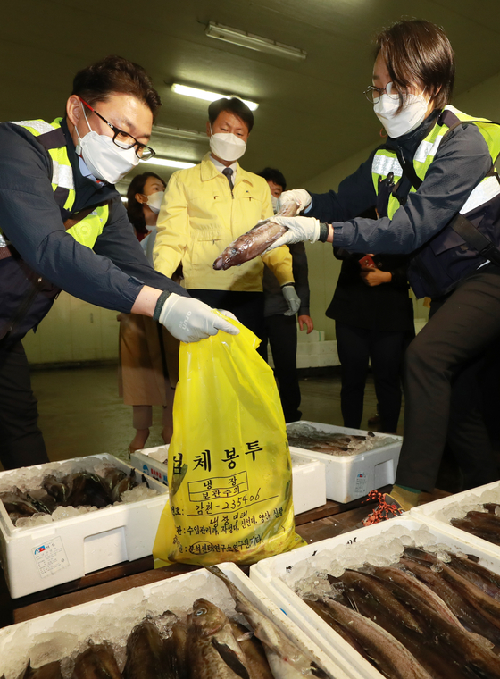 Local inspectors from the Ministry of Food and Drug Safety collect samples for radiation testing of imported Japanese marine products, at Gamcheon Port, Busan, on Monday. [YONHAP]