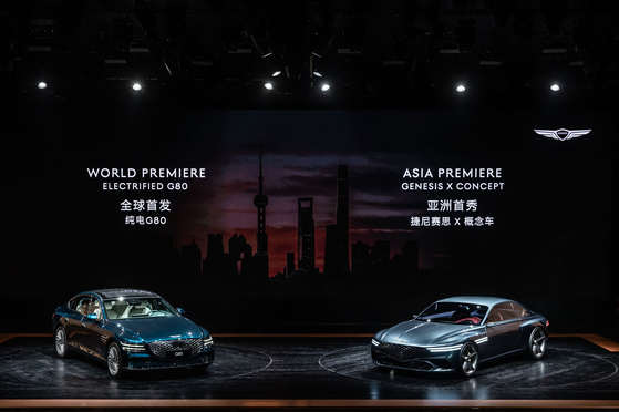 An electric version of the Genesis G80, left, and Genesis X concept model are on display at the Shanghai International Automobile Industry Exhibition on Monday. [HYUNDAI MOTOR]