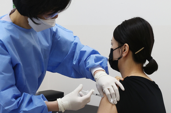 An airline crewmember receives an AstraZeneca shot in a hospital in Gangseo District, Seoul on Monday, as the country rolls out vaccinations for care workers and airline crew. [YONHAP]