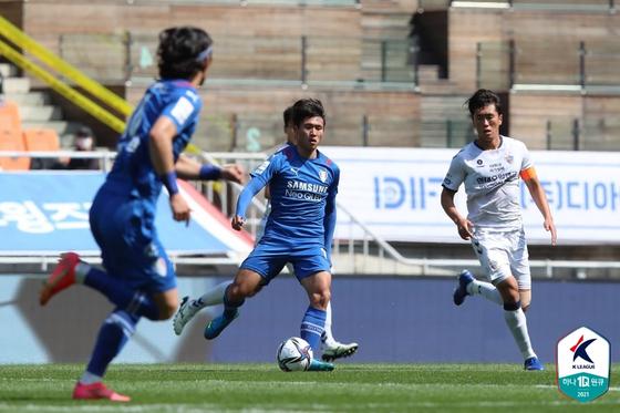 Nineteen-year-old Jeong Sang-Bin of the Suwon Bluewings, center, dribbles the ball in a game against Ulsan Hyundai FC at Suwon World Cup Stadium in Suwon, Gyeonggi on Sunday. [YONHAP]