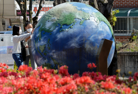 Children explore a globe set up in Geumsan County, South Chungcheong, on Monday. The globe was set up to mark Earth Day on April 22.   [KIM SEONG-TAE]