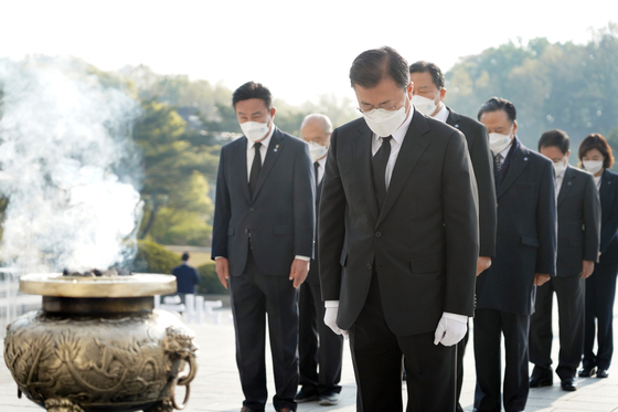 President Moon Jae-in, foreground, pays silent tribute at the monument at the April 19th National Cemetery in northern Seoul on Monday to commemorate the April 19 uprising. [YONHAP]