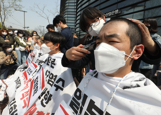 Members of an association of university students shave their heads in protest of Japan's decision to release contaminated water into the Pacific Ocean in front of the Japanese Embassy in central Seoul Tuesday. [NEWS1]