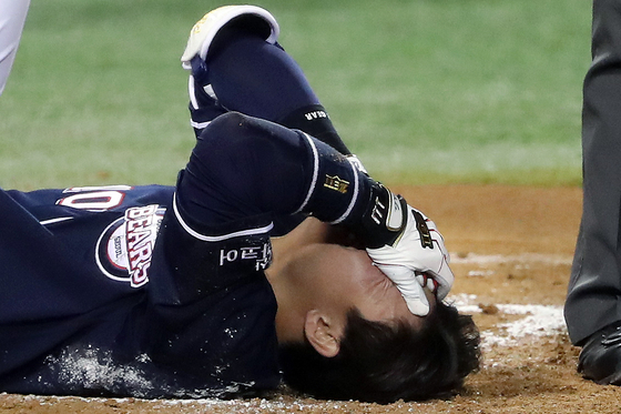 Park Sei-hyok lies on the floor in agony after getting hit in the head by a pitch during the eighth inning of a game between the Doosan Bears and LG Twins at Jamsil Baseball Stadium in southern Seoul on Friday. [NEWS1]