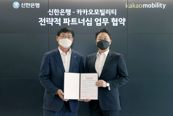 Shin Yeon-sik, deputy president and head of corporate banking at Shinhan Bank, left, and Kakao Mobility Chief Financial Officer Lee Chang-min pose for a photo after signing a partnership deal on April 14 at Kakao Mobility headquarters in Pangyo, Gyeonggi. [SHINHAN BANK]