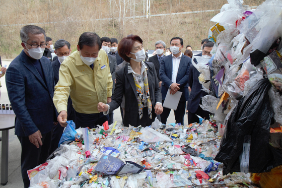 Environment Minister Han Jeoung-ae, center, visits EcoCreation, a company that converts plastic waste into renewable energy, in Okcheon County in North Chungcheong on March 26 to check on plastic wastes that will undergo a pyrolysis process to produce alternative fuel. [ENVIRONMENT MINISTRY]