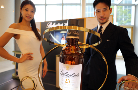Models promote Ballantine's 23-year-old whiskey at Lotte Department Store's World Tower branch in Songpa District, southern Seoul on Wednesday. The premium whiskey, which was previously only available to purchase in duty free stores, is now available in department stores across the country. [YONHAP]