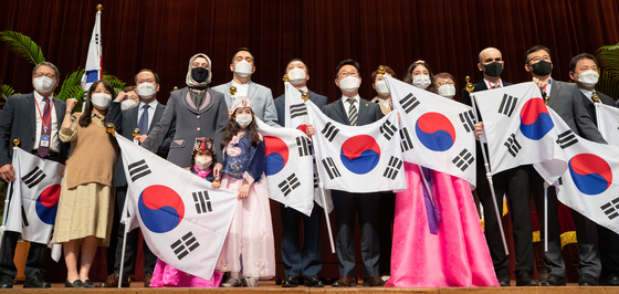 At the Central Government Complex in Gwacheon, Gyeonggi, on Wednesday, Justice Minister Park Beom-kye, center, poses for a photo with a group of expats who were naturalized through special procedure, after awarding them their certificate of Korean citizenship. [NEWS1]