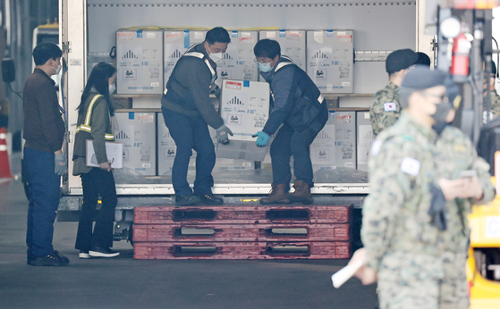 Workers unload 250,000 doses of the Pfizer Covid-19 vaccine which arrived at Incheon International Airport on Wednesday. The shipment is part of 26 million doses for the inoculation of 13 million people that Korea will introduce this year under a contract with the U.S. drug company. [YONHAP]