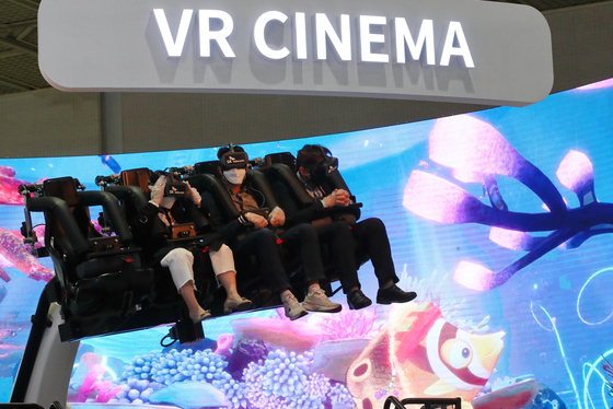 Visitors to the World IT Show experience virtual reality (VR) cinema at SK Telecom's booth in Coex, southern Seoul on Wednesday. The event will run until April 23. [YONHAP]