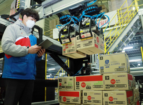 A CJ Logistics employee operates robotic arms to move around boxes at one of the logistics company's warehouses. The company on Thursday announced the commercial use of the artificial intelligence-operated robotic system in its conveyor line. [CJ LOGISTICS]