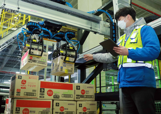 A CJ Logistics worker demonstrates an AI robot depalletizer at a fulfilment center in Dongtan, Gyeonggi. [CJ LOGISTICS]