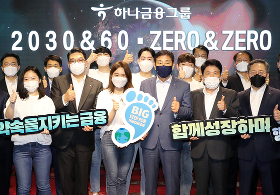 Hana Financial Group Chairman Kim Jung-tai, third from right in front, poses with group officials during an event held Thursday to announce the group's vision to achieve carbon neutrality by 2050 at H-Pulse, a lounge operated by Hana Bank for members of the group's loyalty program, Hana Members, in Mapo District, western Seoul. [HANA FINANCIAL GROUP]