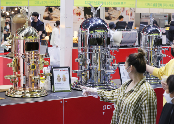 A customer checks out a coffee machine at the Seoul Cafe and Bakery Fair held at Setec in Seoul on Thursday. [YONHAP]