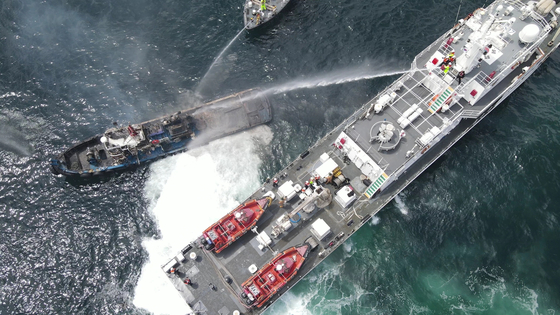 Coast guard ships extinguish a fire on a tugboat off Samcheok, Gangwon, on Saturday. The tugboat sank and two sailors were rescued. [NEWS1]