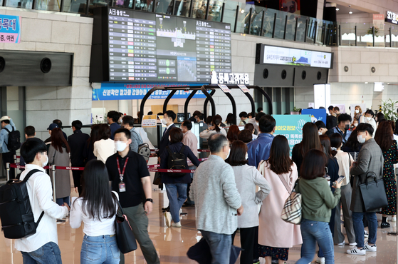 The domestic terminal of Gimpo International Airport is crowded with travelers on Sunday. As overseas travel was shut down due to Covid-19 , travelers increasingly choose domestic travel instead. [YONHAP]