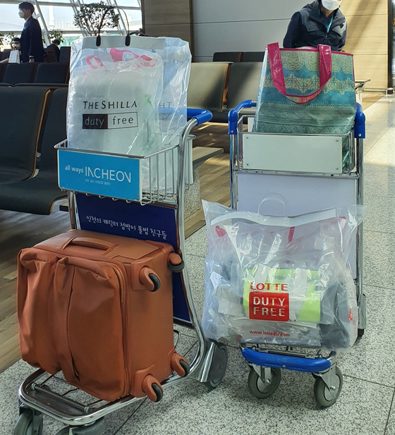 Many passengers need luggage carts to carry all the duty-free goods they purchased. [HALEY YANG]