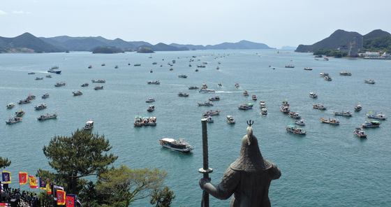 Fishing boats in the sea off Tongyeong, South Gyeongsang, on Monday protest Japan's decision to dump contaminated water into the Pacific Ocean. The statue of Admiral Yi Sun-shin, a national hero who beat invading Japanese war ships in 1592, looks over the sea. [YONHAP]
