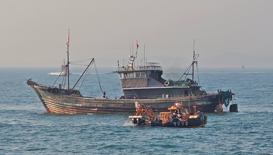 A South Korean Coast Guard vessel approaches a Chinese boat fishing illegally near Yeonpyeong Island on April 19. [YONHAP]