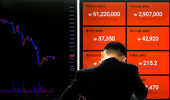 A passerby looks at prices of cryptocurrencies including bitcoin on a digital signboard operated by a local cryptocurrency exchange, Bithumb, in Gangnam District, southern Seoul, on Monday. Bitcoin prices on Monday slightly recovered from their fall to 55 million won ($49500) last week. [YONHAP]