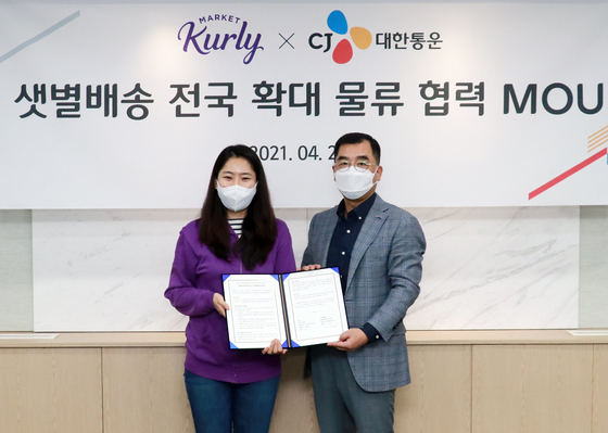 Kurly CEO Sophie Kim, left, and Kang Sin-ho, CEO at CJ Logistics, sign to cooperate on delivery of Market Kurly's fresh produces at CJ Logistics headquarters in central Seoul on Tuesday. [CJ LOGISTICS]